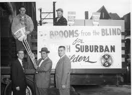 "An antique photo showing men with a truck selling ""brooms from the blind"" according to the sign"