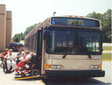 A port authority bus from the 1970s with its wheelchair ramp extended, loading some passengers