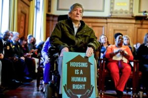 "A man in a wheelchair sits in a courtroom with a bunch of other folks, he holds a sign that says ""Housing is a human right"""