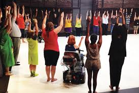 People at a workshop doing a group exercise, hands raised, the woman in the center is participating while in a wheelchair