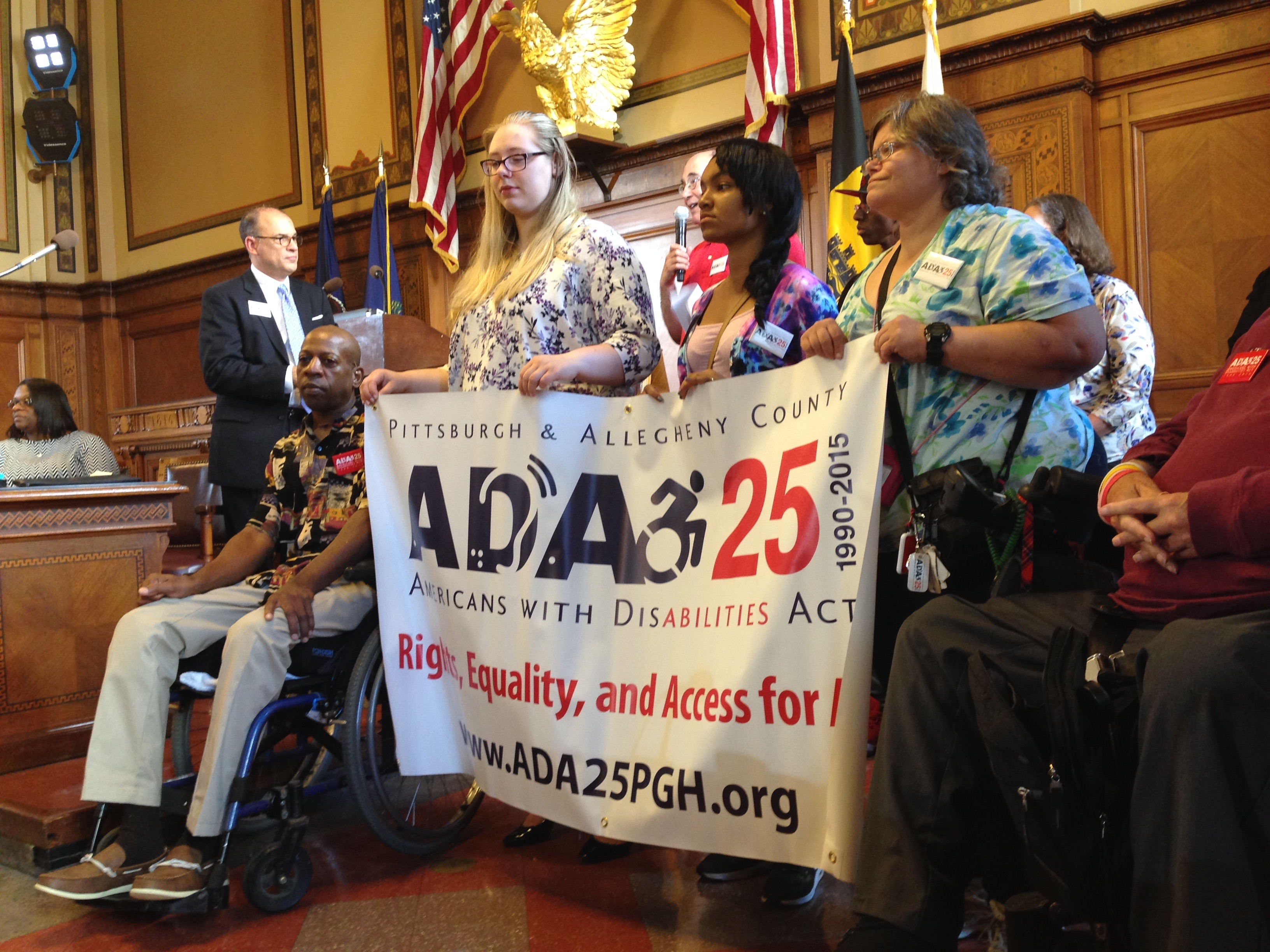 Group of people at a Pittsburgh City Council meeting hold a large banner commemorating the 25th anniversary of the ADA