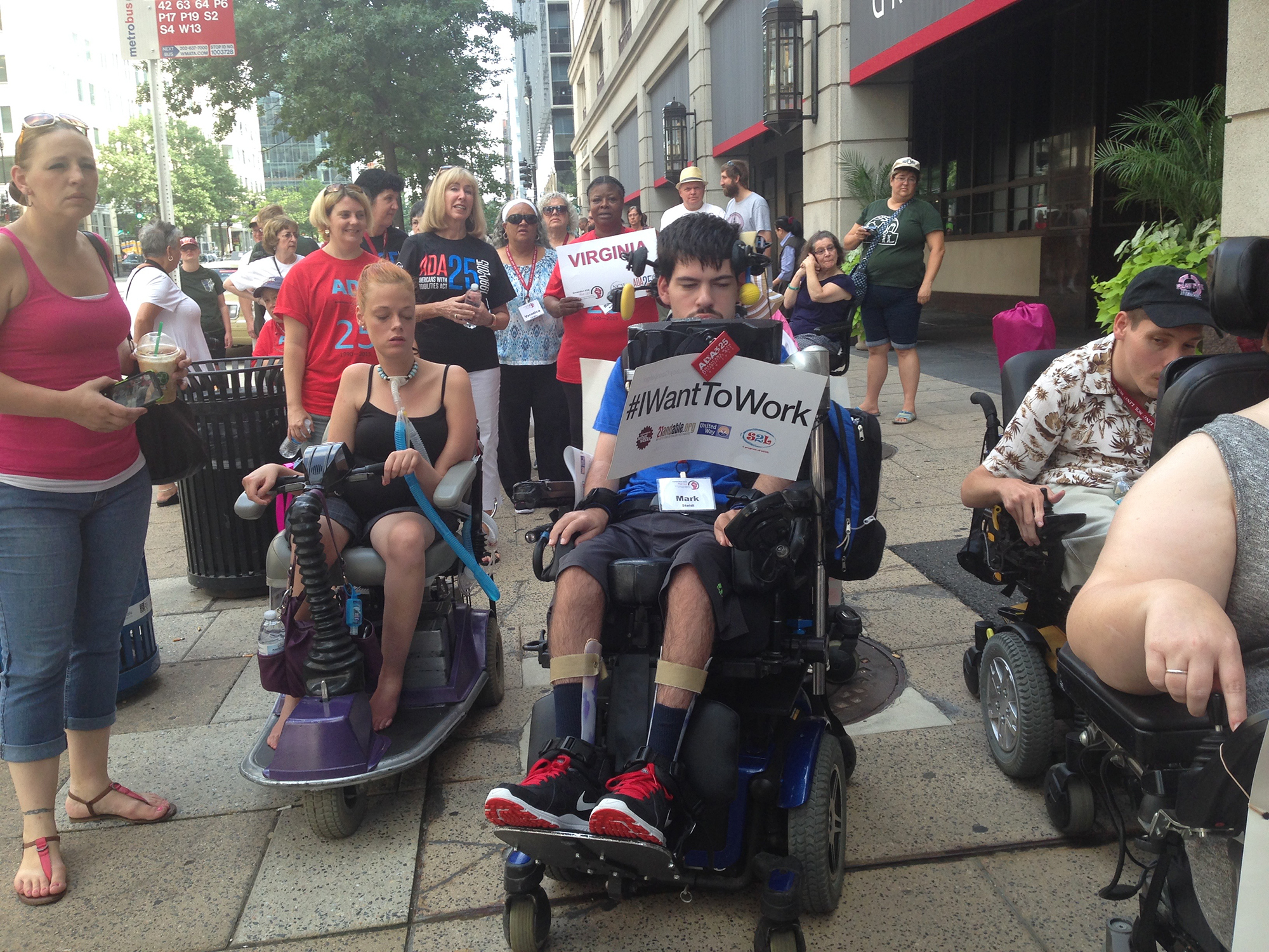 "Young man sitting in wheelchair participates in street march, holding a sign that reads: ""I Want to Work."""
