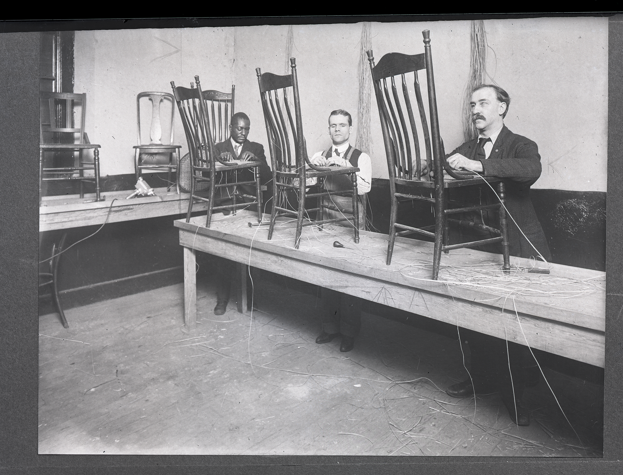 Historic photo shows three blind men weaving chair seats.