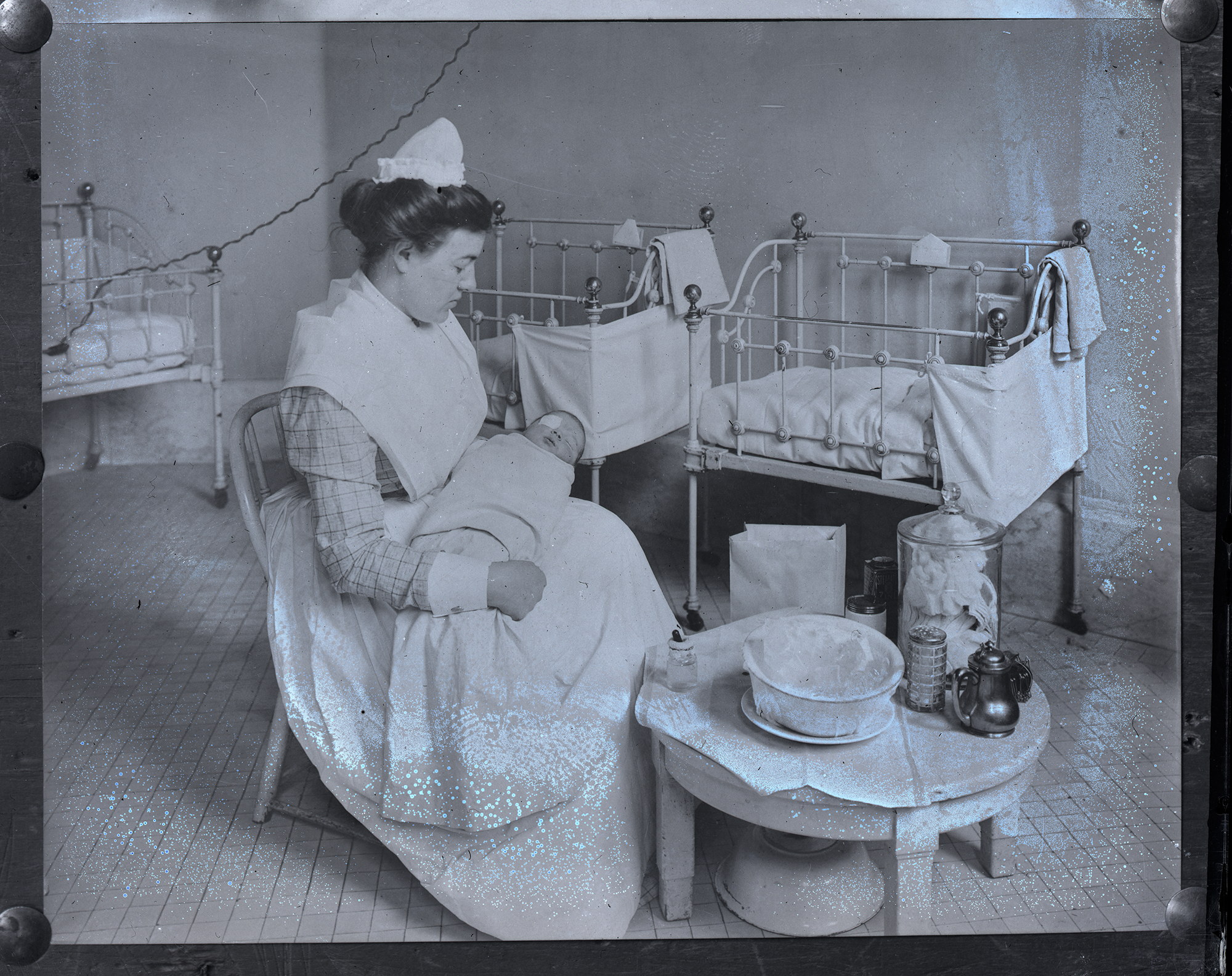 Historic photo shows nurse caring for blind infant.