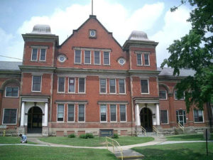 The front of the Mayview Building, brick, three stories with a wide lawn before it