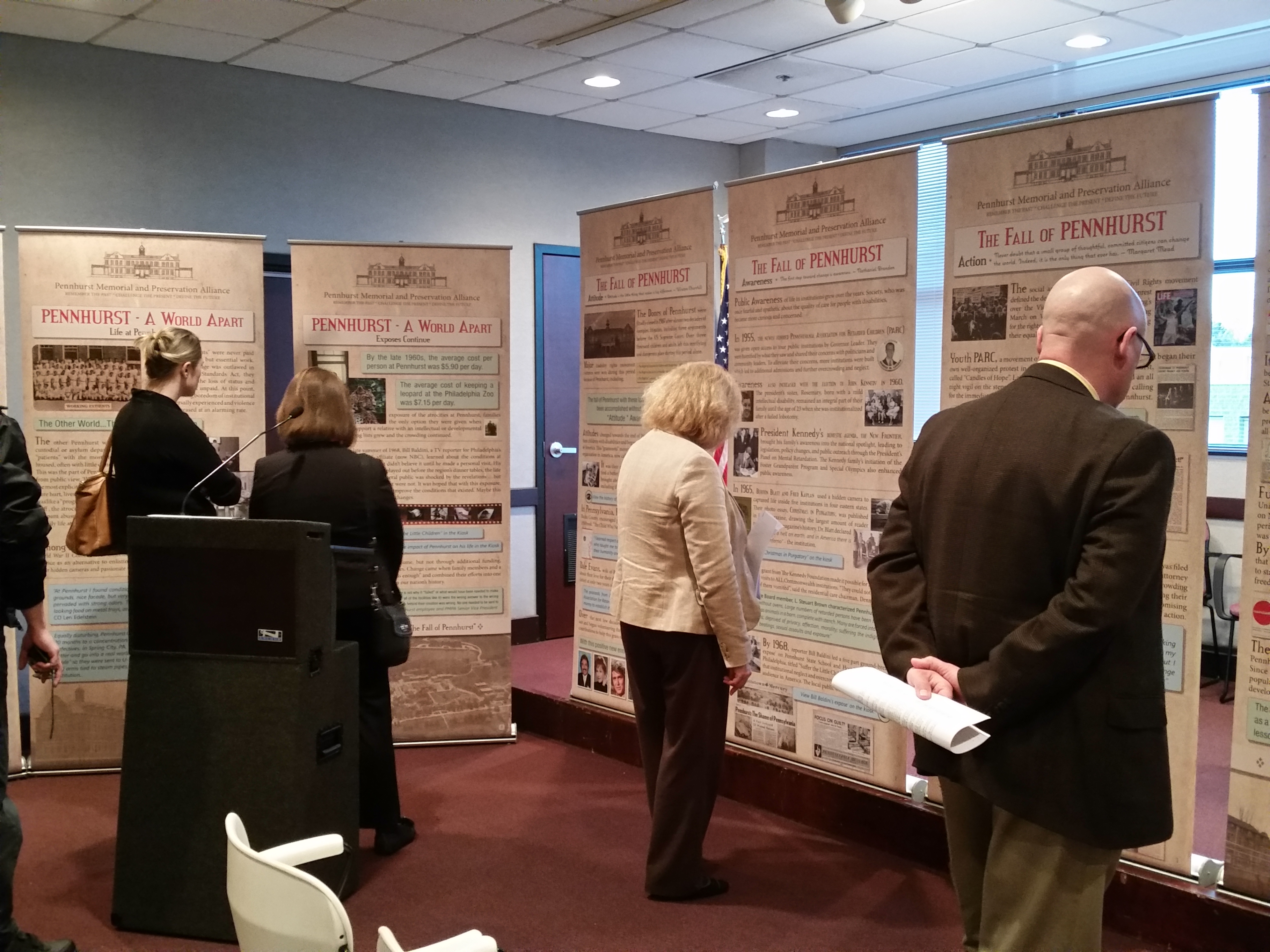People viewing Pennhurst displays, which are banner signs placed around a conference room