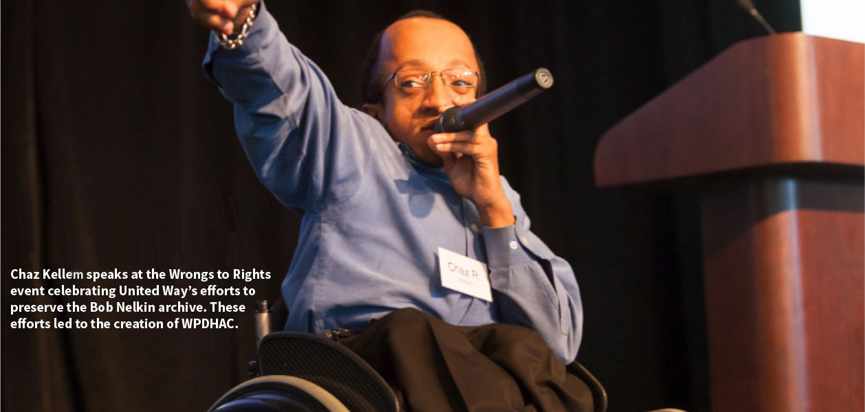 Chaz Kellem, a black man using a wheelchair, wears a blue button down and black dress pants. He is behind a podium holding a microphone to his mouth and pointing out at the audience.