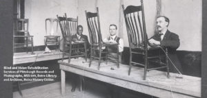 Old black and white photo of men who are blind caning chairs at a long table.