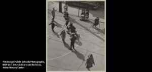 A black and white photo of children playing on a basketball court at Bedford School in nineteen fifty seven. Two children are seated in wheelchairs. Several are using crutches.