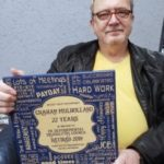Photo of Graham Mulholland holding a retirement plaque for 22 years service.