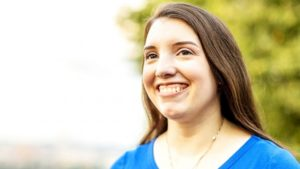 Head shot of Jessica Benham. She has long brown hair and a big smile.