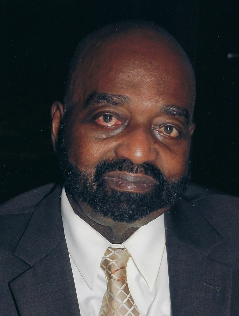 Reverend Dr. Holbrook, an older black man with a beard and mustache, wearing a suit