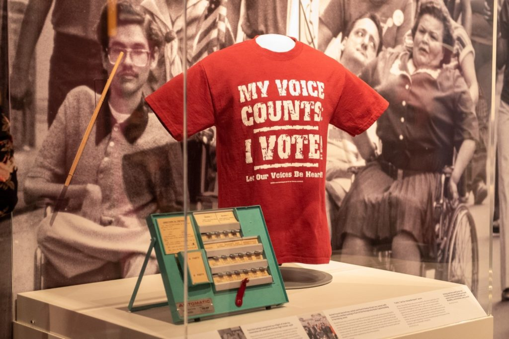 Artifacts from Paul Dick and Rachel Freund on display in American Democracy: A Great Leap of Faith. From left to right: dowel rod used by Paul to vote, voting machine used by Rachel to train voters, and Let Our Voices Be Heard t-shirt worn by Rachel. The backdrop is a black and white image of disability rights activists including Eileen Shackleton and Ray Smith marching in a parade. Image Source: Senator John Heinz History Center