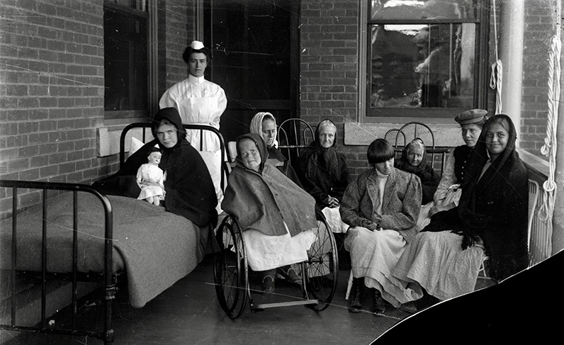 Black and white image of institutionalized women in the company of a nurse on a porch at Polk State Center, c. 1900s-1920s.