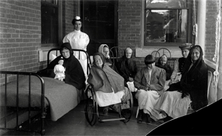 Black and white photo of institutionalized women in the company of a nurse on a porch at Polk State Center, c. 1900s-1920s. Photo courtesy of Senator John Heinz History Center.
