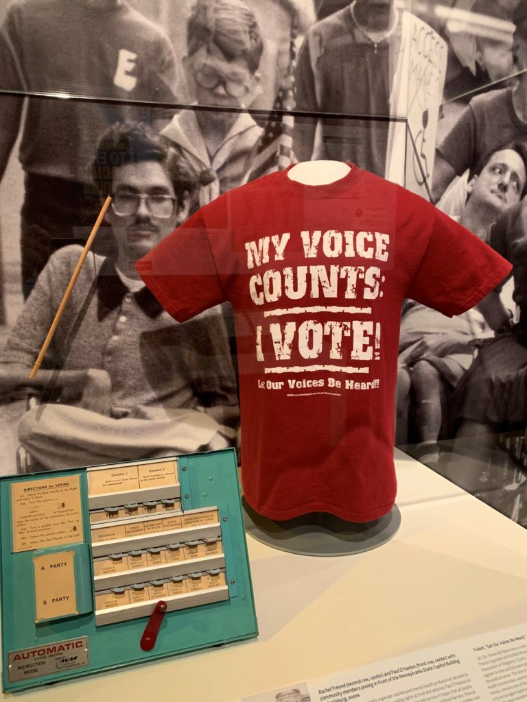 """Photo shows detail from the disability rights segment of the American Democracy exhibit. On the right is a red T-shirt with the words """"My Voice Counts: I Vote"""" in large white letters. On the left is a voting machine used in an advocacy effort to educate voters with disabilities."""