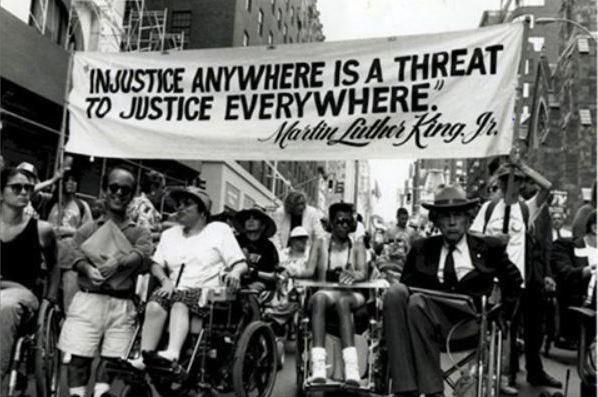"""Photo shows a disability rights march in on a city street. Above the marchers is a banner with a quote from Martin Luther King that reads: """"Injustice anywhere is a threat to justice everywhere."""""""